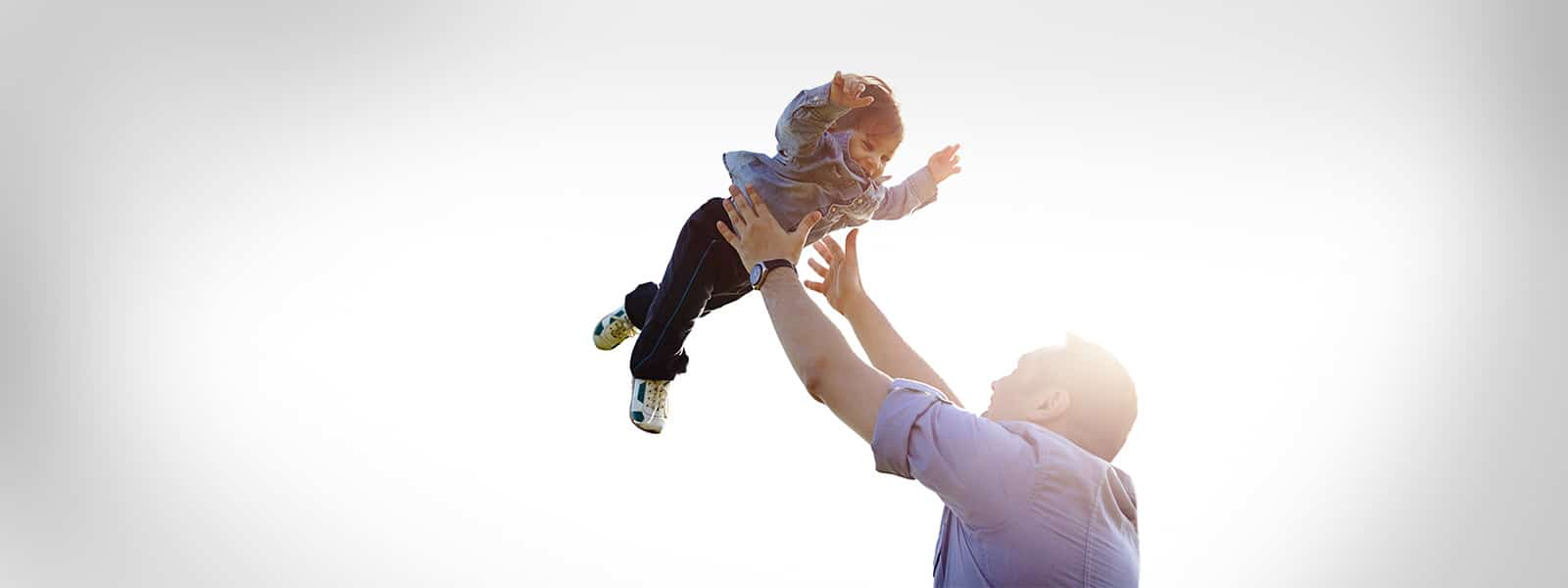 man playing with his child and throwing him in the air