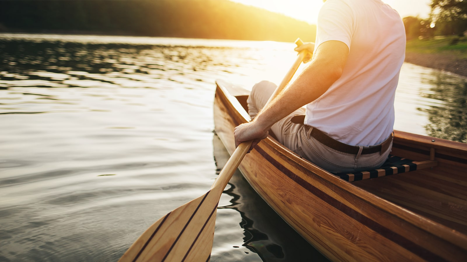 close up of the oar as a man sits in a canoe