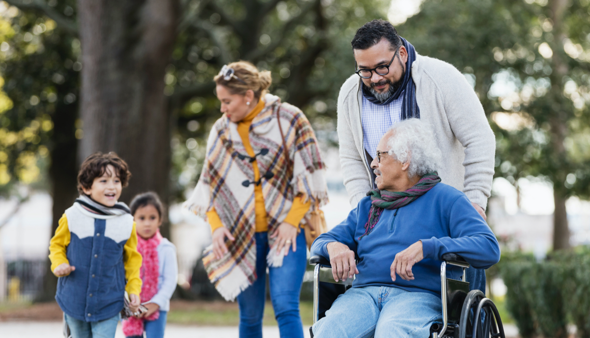 Family outdoors,  including grandmother in wheelchair, parents and two children