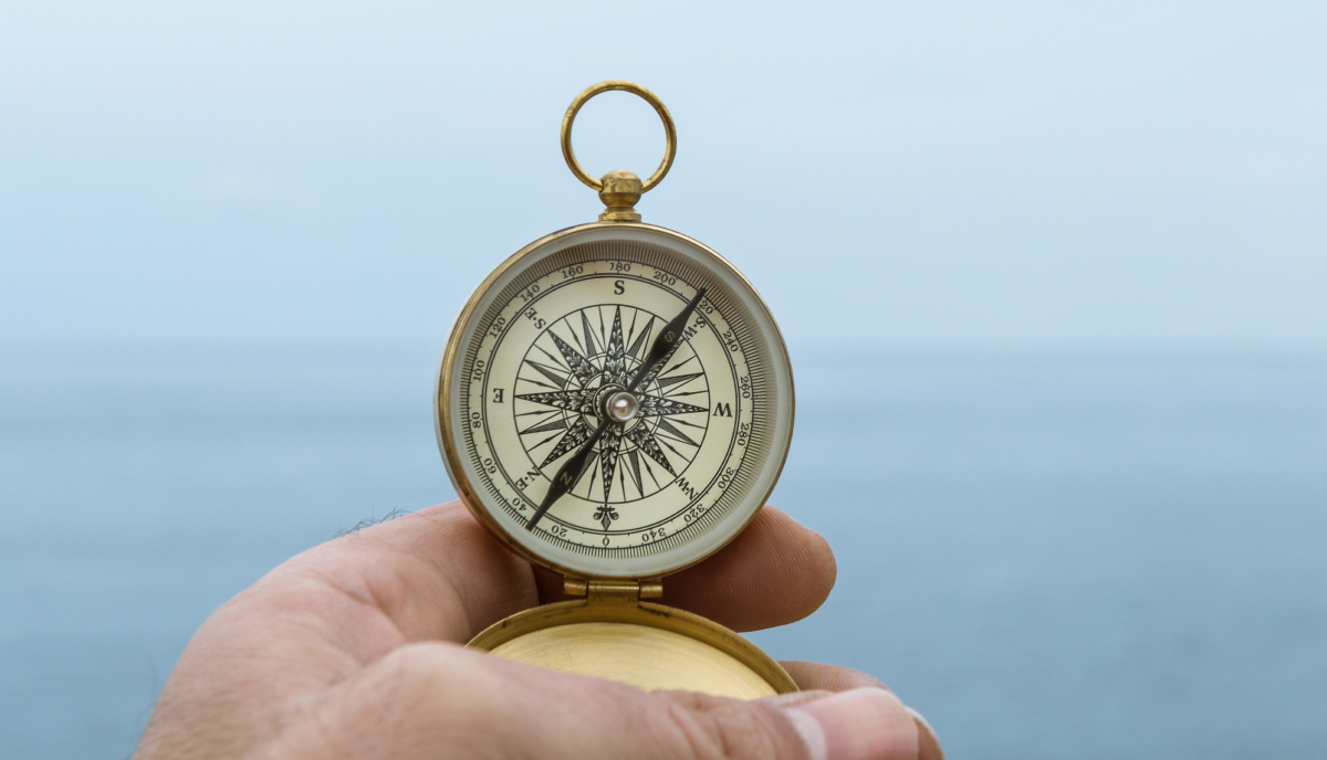 a hand holding a compass with the sea in the background