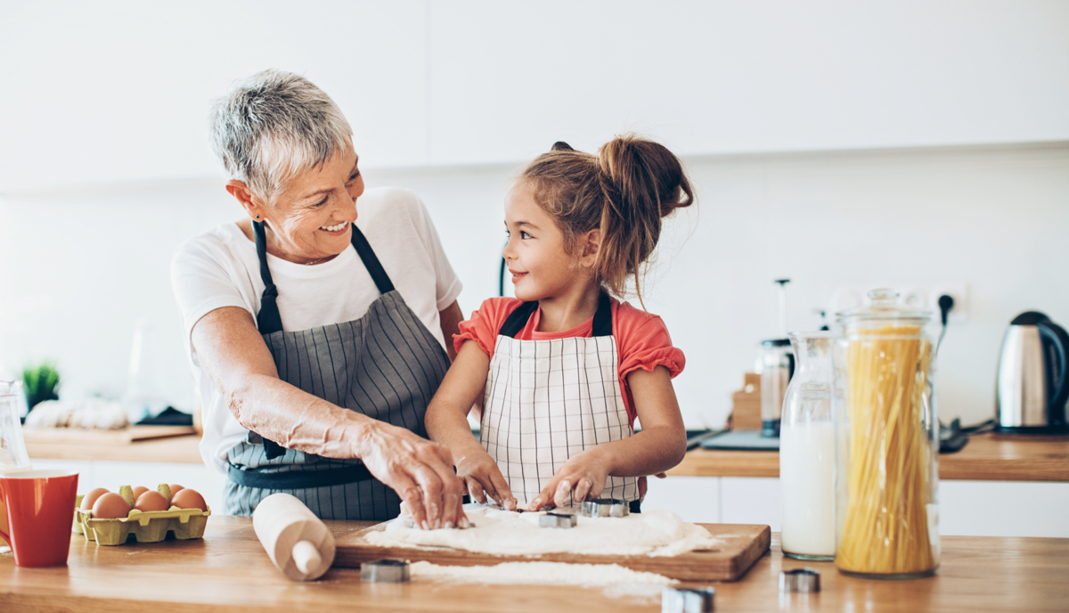 older woman and young girl making food in kitchen
