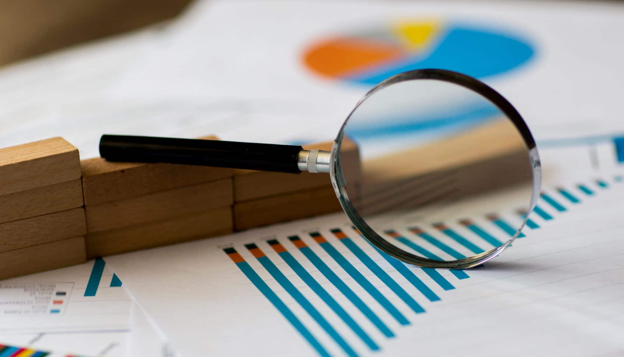 Magnifying glass over papers with charts